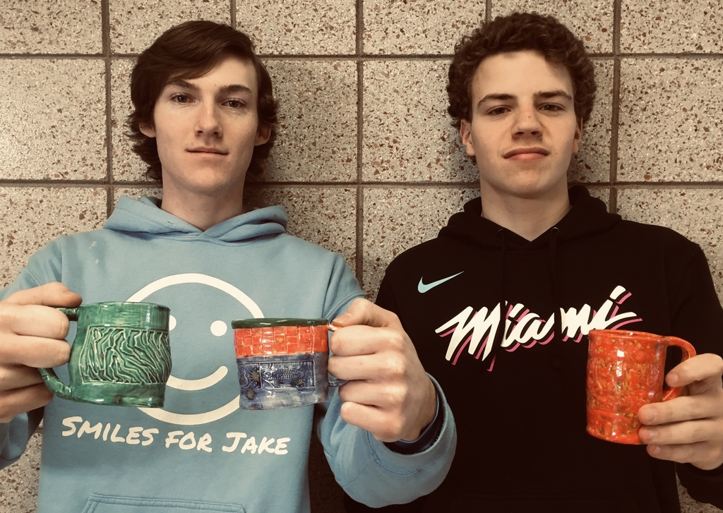 two male students with mugs from art class