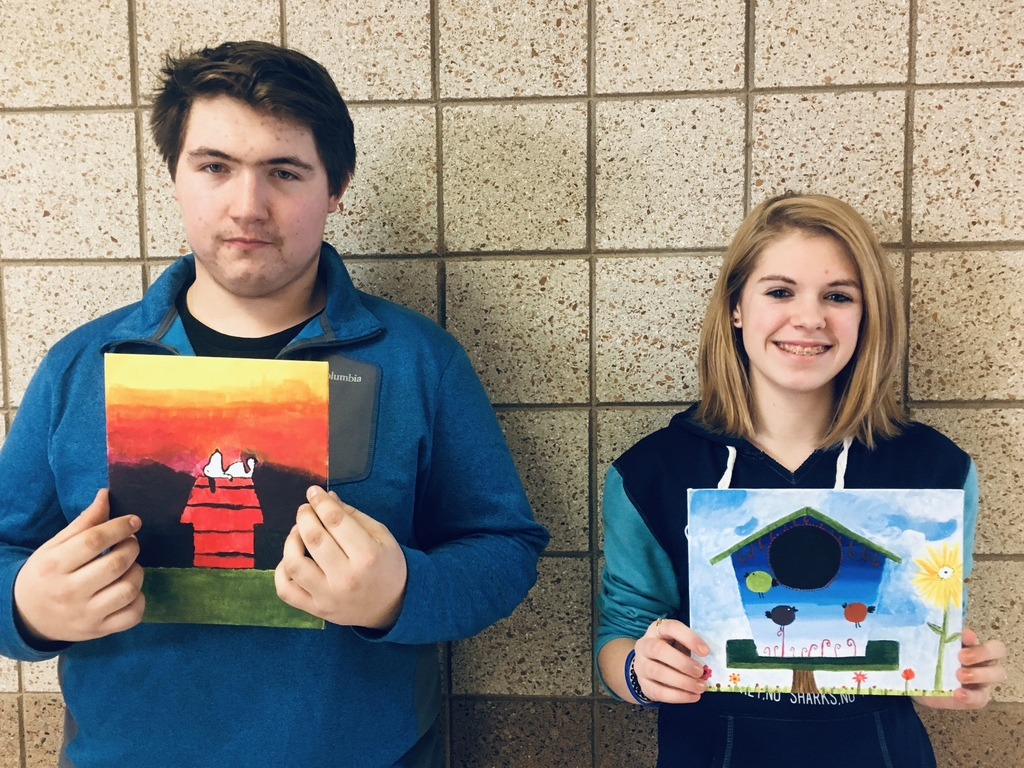 one male and one female student with paintings