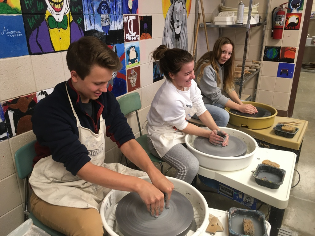 a male and two females on a pottery wheel