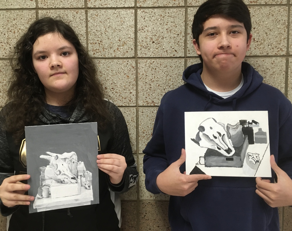 two students displaying their artwork