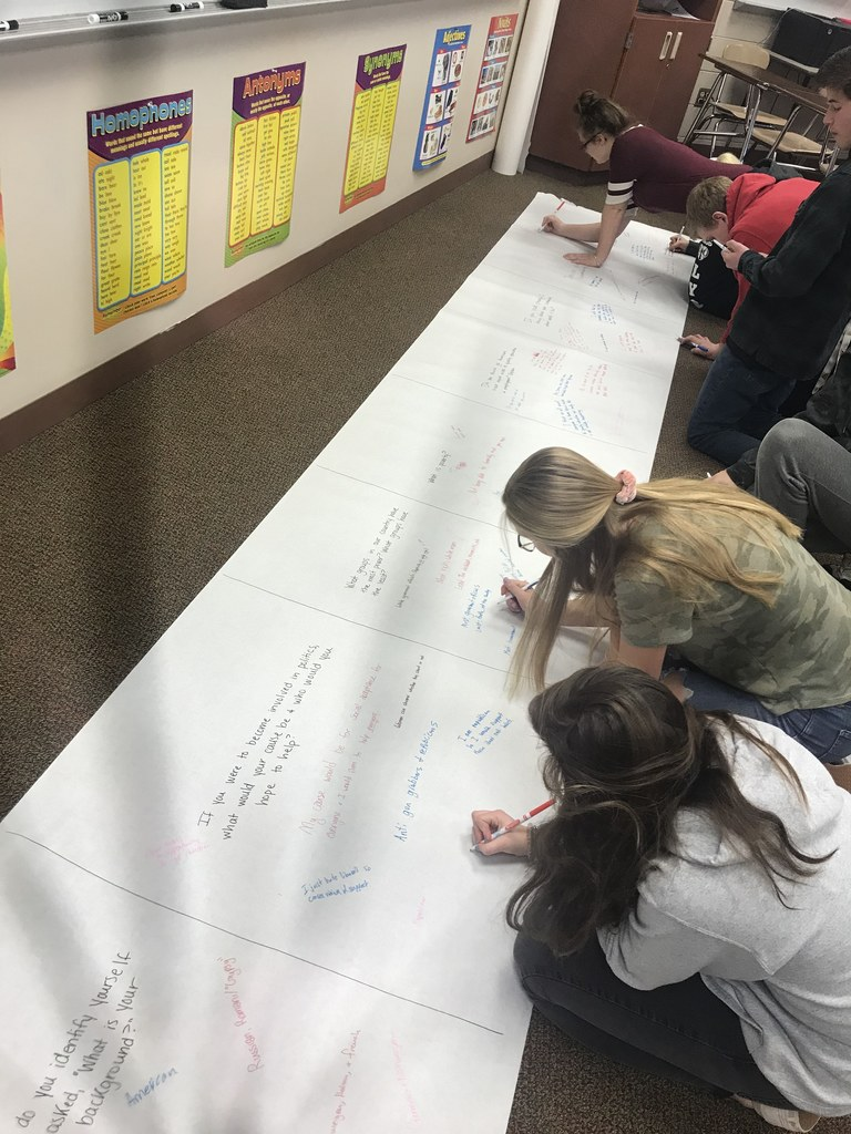 two students write on large white paper