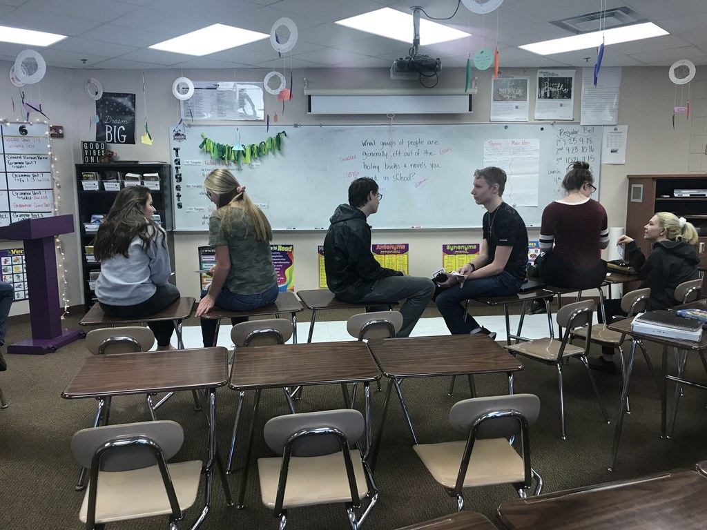 male and female students sitting on desks