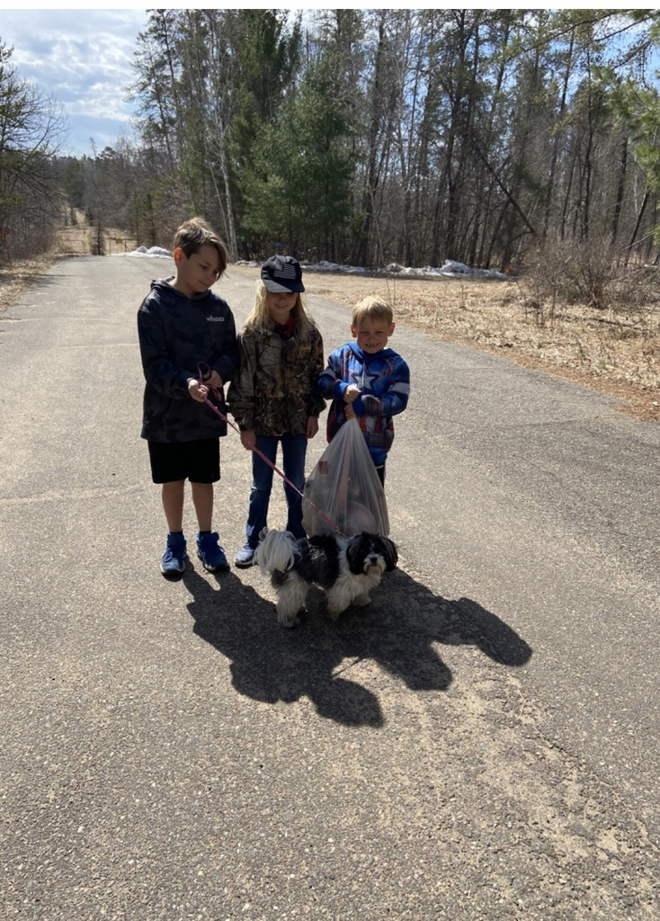 female and 2 male students with garbage and a dog