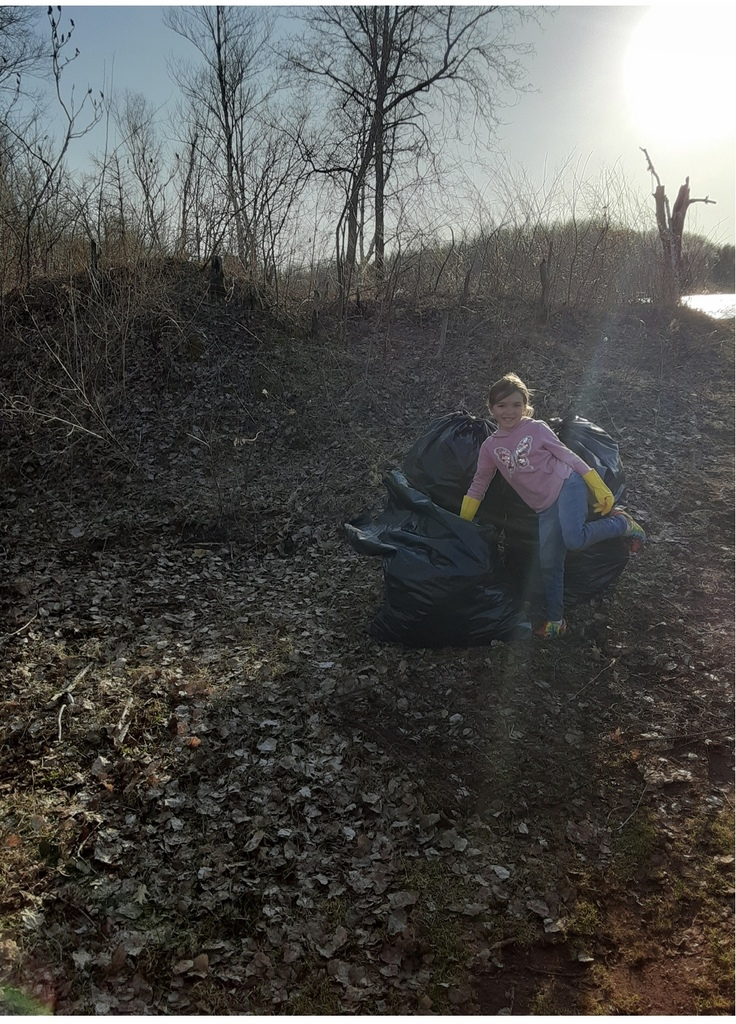 female student in the woods with garbage bags