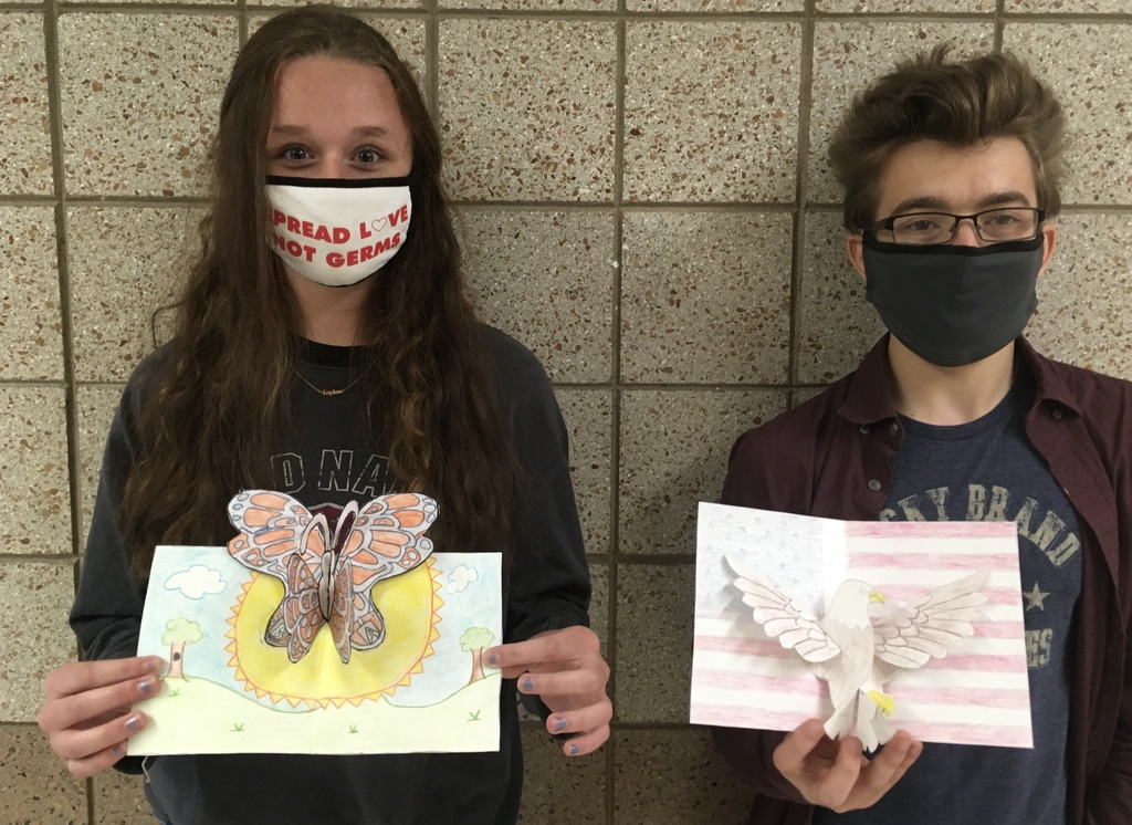 female and male student with their art creations